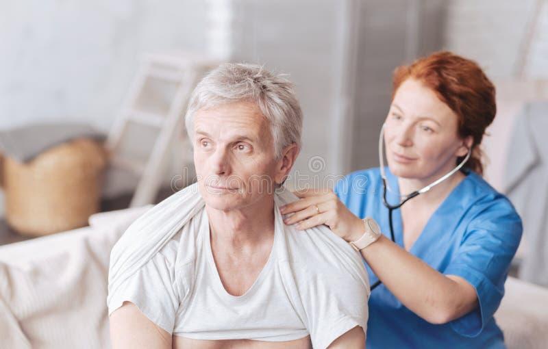 Enfermera alegre con el estetoscopio que escucha los sonidos del pulmón del paciente imagenes de archivo