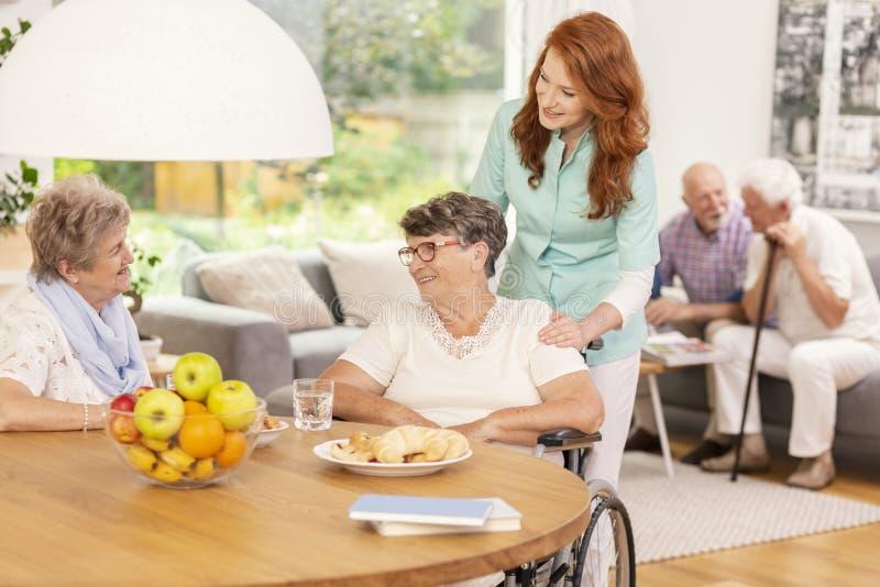 Enfermera amistosa que apoya a la mujer enferma inhabilitada en una silla de ruedas du imagenes de archivo