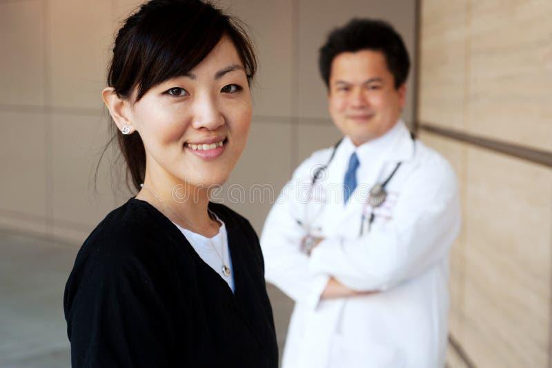 Enfermera asiática con el doctor en fondo fotografía de archivo libre de regalías