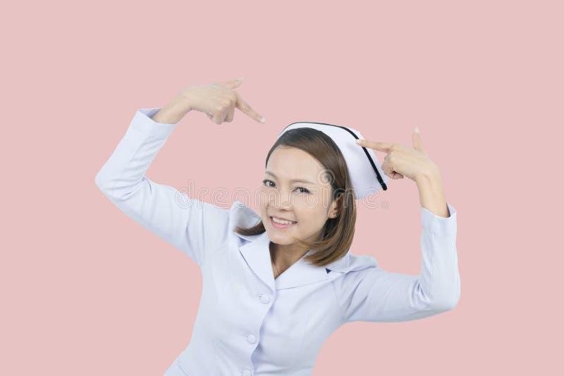 Enfermera asiática de la sonrisa en fondo rosado imagen de archivo