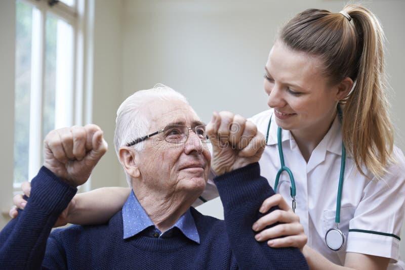 Enfermera Assessing Stroke Victim aumentando los brazos foto de archivo libre de regalías