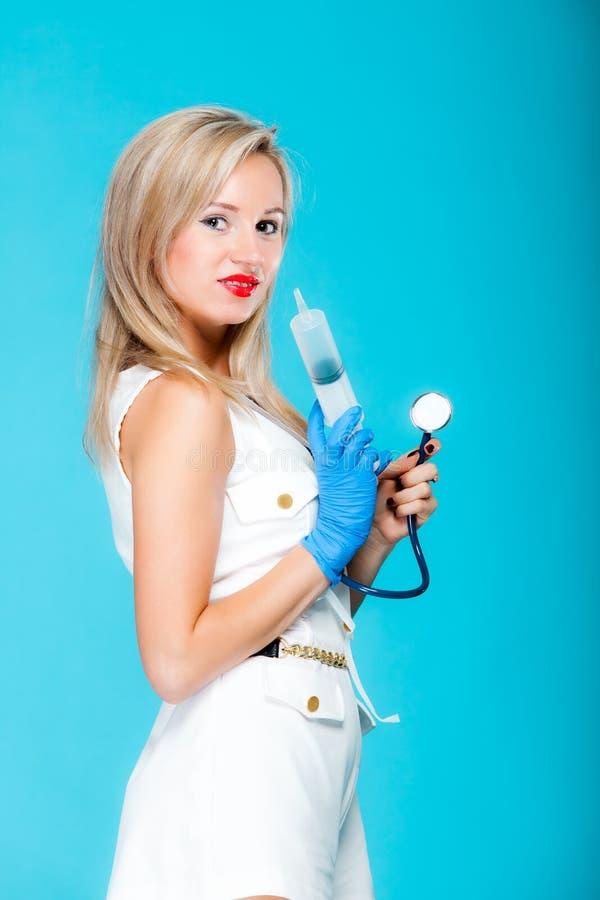Enfermera atractiva divertida del doctor de la muchacha con el estetoscopio de la jeringuilla fotografía de archivo libre de regalías