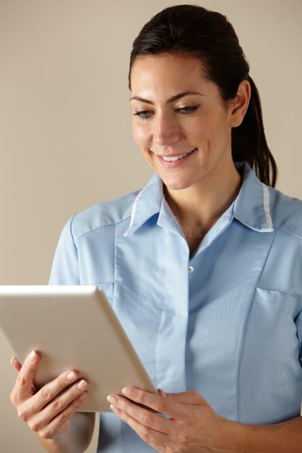 Enfermera BRITÁNICA que usa la tablilla del ordenador fotos de archivo libres de regalías