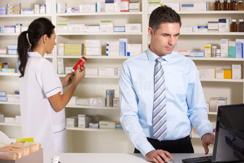 Enfermera BRITÁNICA y farmacéutico que trabajan en farmacia foto de archivo