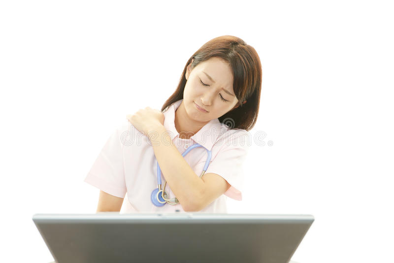 Enfermera con dolor de cuello del hombro. imágenes de archivo libres de regalías