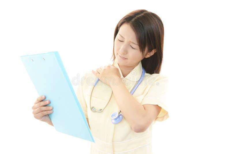 Enfermera con dolor del hombro. imagen de archivo