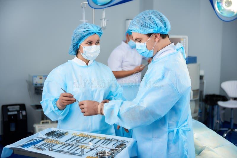 Enfermera de la calma que mira al cirujano y que le da los instrumentos médicos foto de archivo libre de regalías