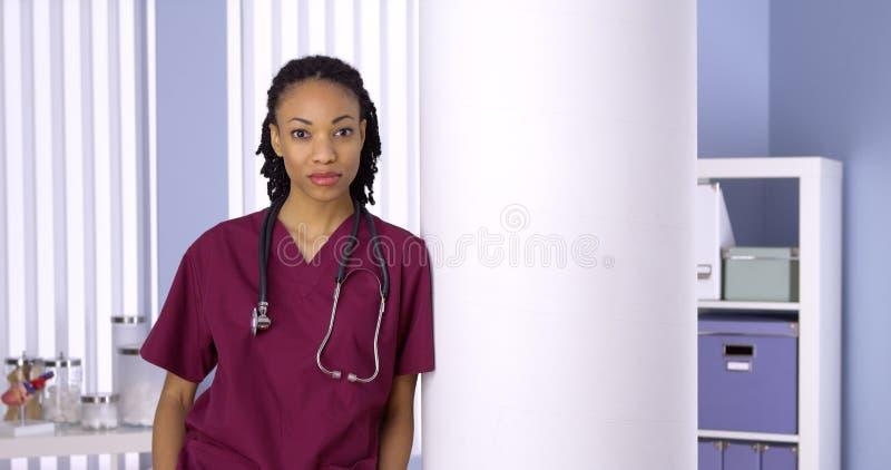 Enfermera de la mujer negra que se coloca en oficina imágenes de archivo libres de regalías
