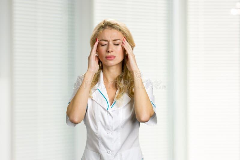 Enfermera de los jóvenes con dolor de cabeza fuerte imágenes de archivo libres de regalías