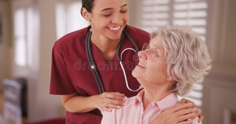 Enfermera de sexo femenino hispánica que mira y que sonríe con el caucásico mayor fotografía de archivo