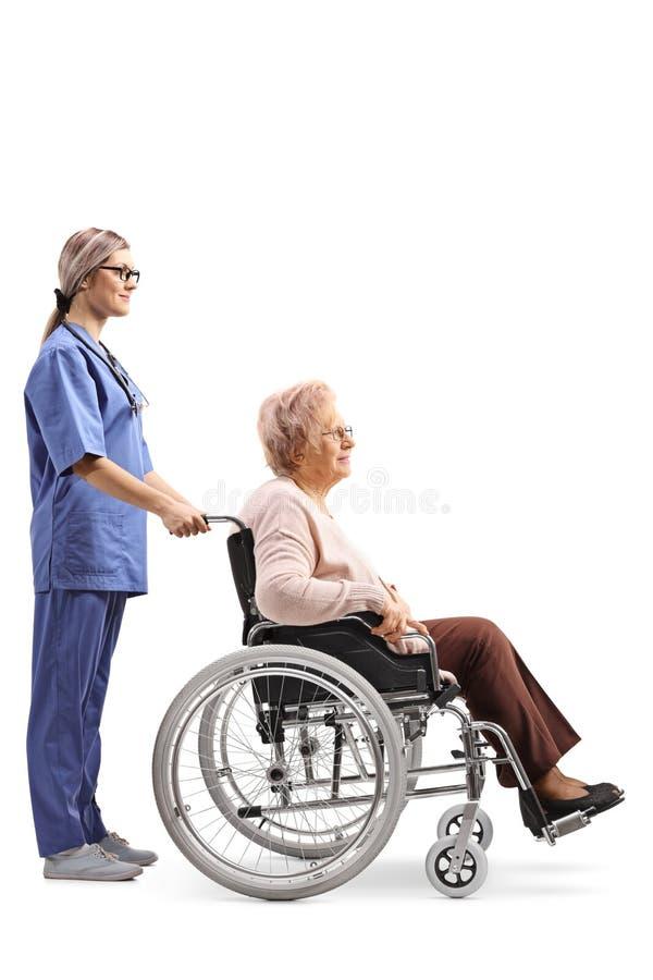 Enfermera de sexo femenino joven que empuja a una mujer mayor en una silla de ruedas imagenes de archivo