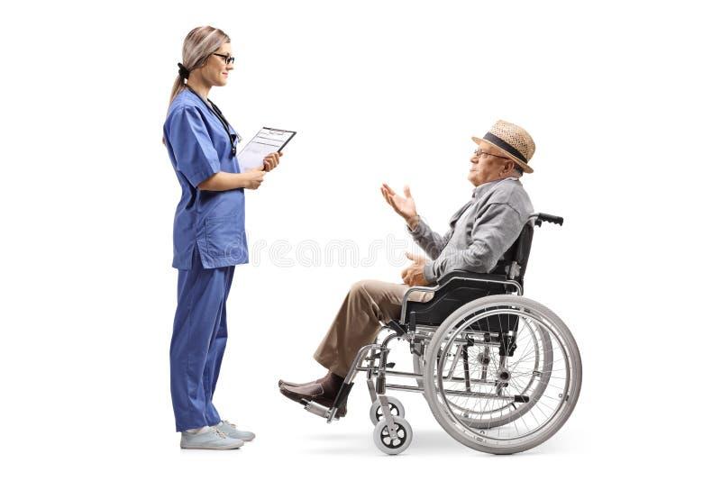 Enfermera de sexo femenino joven que habla con un caballero mayor en una silla de ruedas fotografía de archivo libre de regalías