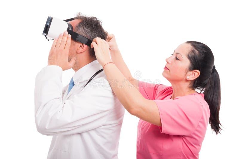 Enfermera de sexo femenino que ajusta los vidrios del vr según el doctor de sexo masculino imagenes de archivo