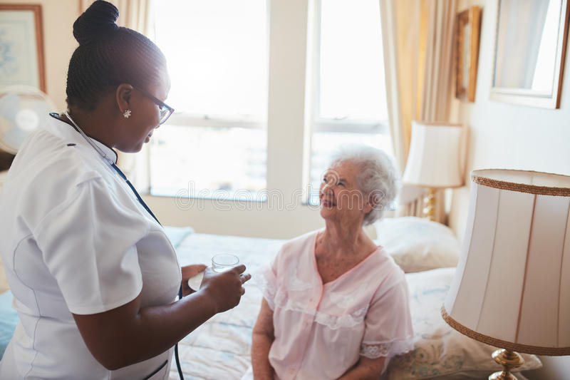 Enfermera de sexo femenino que da la medicina al paciente mayor en casa fotos de archivo libres de regalías