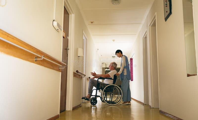 Enfermera de sexo femenino que empuja al paciente masculino mayor discapacitado que se sienta en silla de ruedas fotografía de archivo