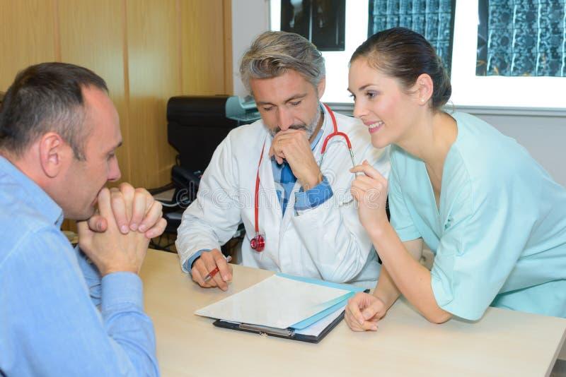 Enfermera de sexo femenino sonriente con el doctor y el paciente imagen de archivo libre de regalías