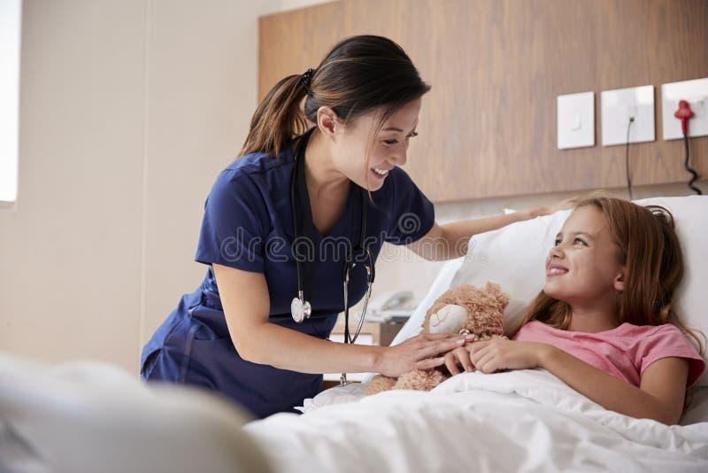 Enfermera de sexo femenino Visiting Girl Lying en la cama de hospital que abraza a Teddy Bear foto de archivo libre de regalías