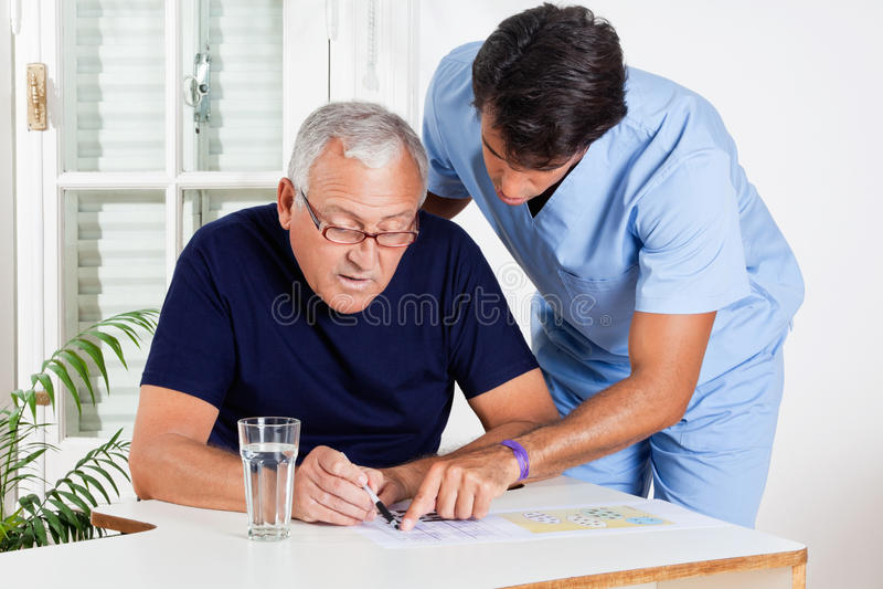 Enfermera de sexo masculino Helping Senior Man en solucionar rompecabezas imagenes de archivo