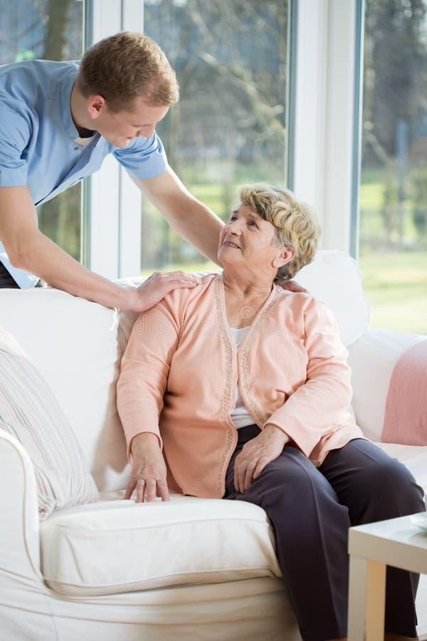 Enfermera de sexo masculino que ayuda a la mujer jubilada imagenes de archivo