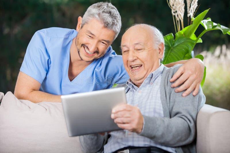 Enfermera de sexo masculino And Senior Man que ríe mientras que mira fotos de archivo libres de regalías