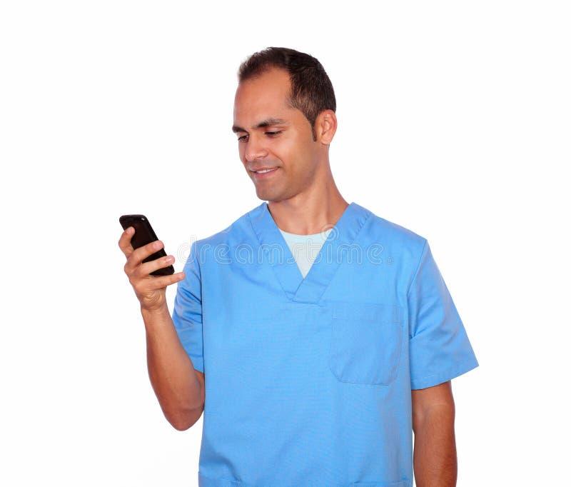 Enfermera de sexo masculino sonriente que envía el mensaje en el teléfono móvil fotos de archivo libres de regalías