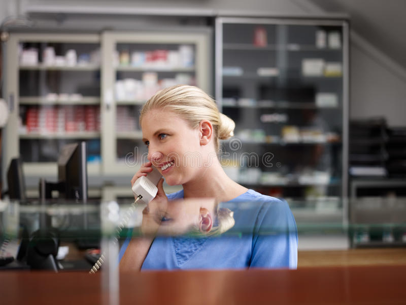 Enfermera en clínica y discurso en el teléfono fotos de archivo libres de regalías