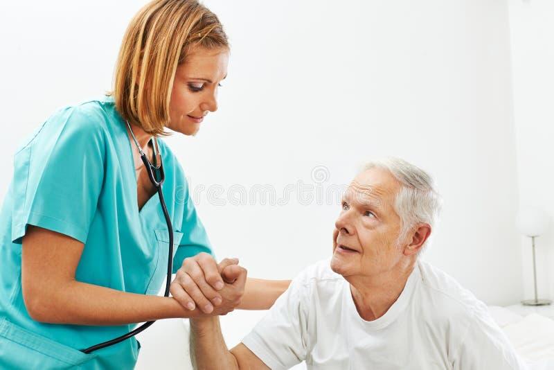 Enfermera en la clínica de reposo que ayuda al hombre mayor fotos de archivo libres de regalías