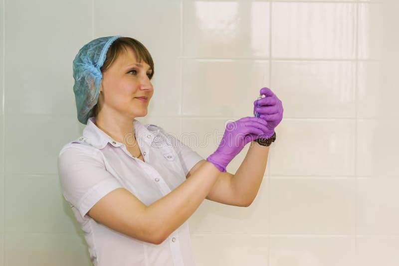 Enfermera en los guantes que preparan la jeringuilla para la inyección foto de archivo