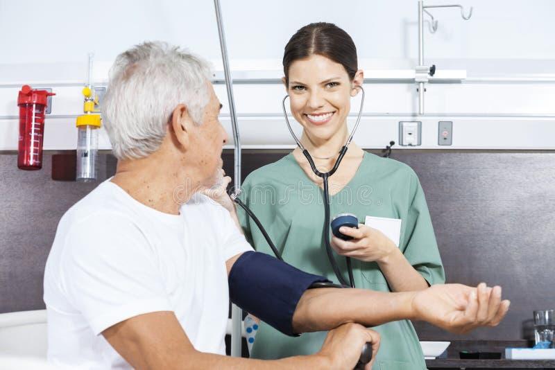 Enfermera feliz Examining Blood Pressure del hombre en centro de rehabilitación fotografía de archivo