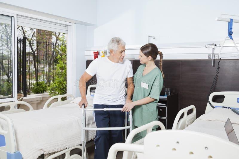 Enfermera Helping Male Patient al usar a Walker At Nursing Home foto de archivo