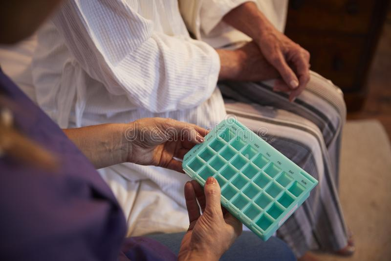 Enfermera Helping Senior Woman para organizar la medicación en la visita casera imágenes de archivo libres de regalías