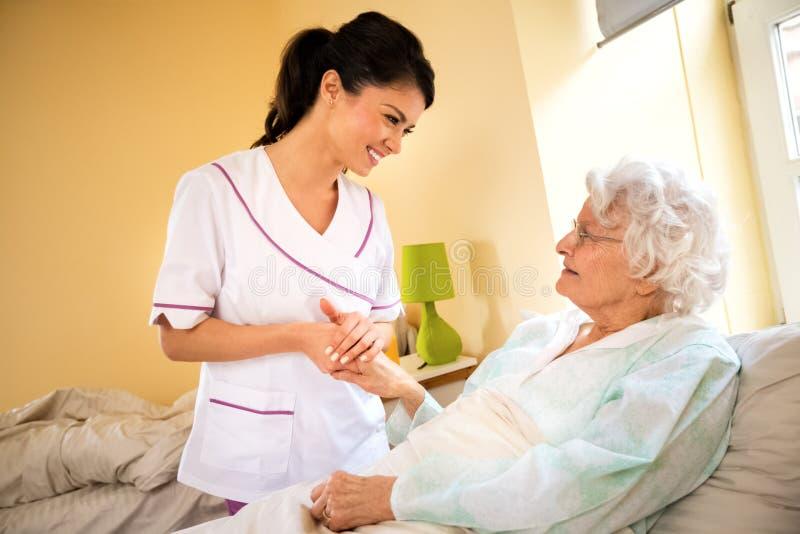 Enfermera hermosa que lleva a cabo la mano del viejo paciente mayor y de la comodidad h fotografía de archivo