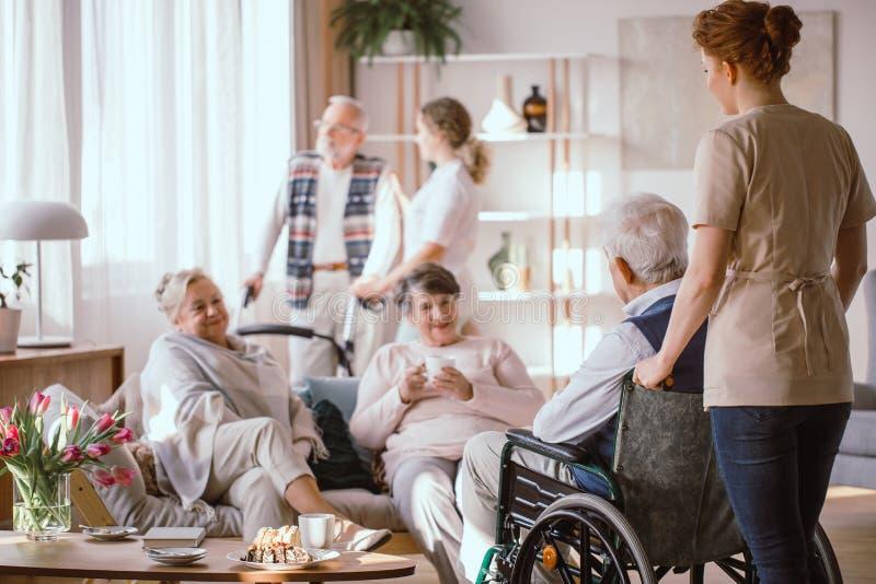 Enfermera joven que lleva al hombre mayor perjudicado en la silla de ruedas a sus amigos imágenes de archivo libres de regalías