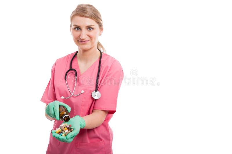 Enfermera médica de la mujer que derrama una botella de píldoras fotografía de archivo libre de regalías