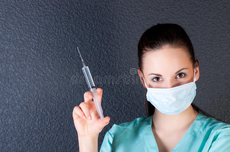 Enfermera o doctor con la jeringuilla y la máscara foto de archivo