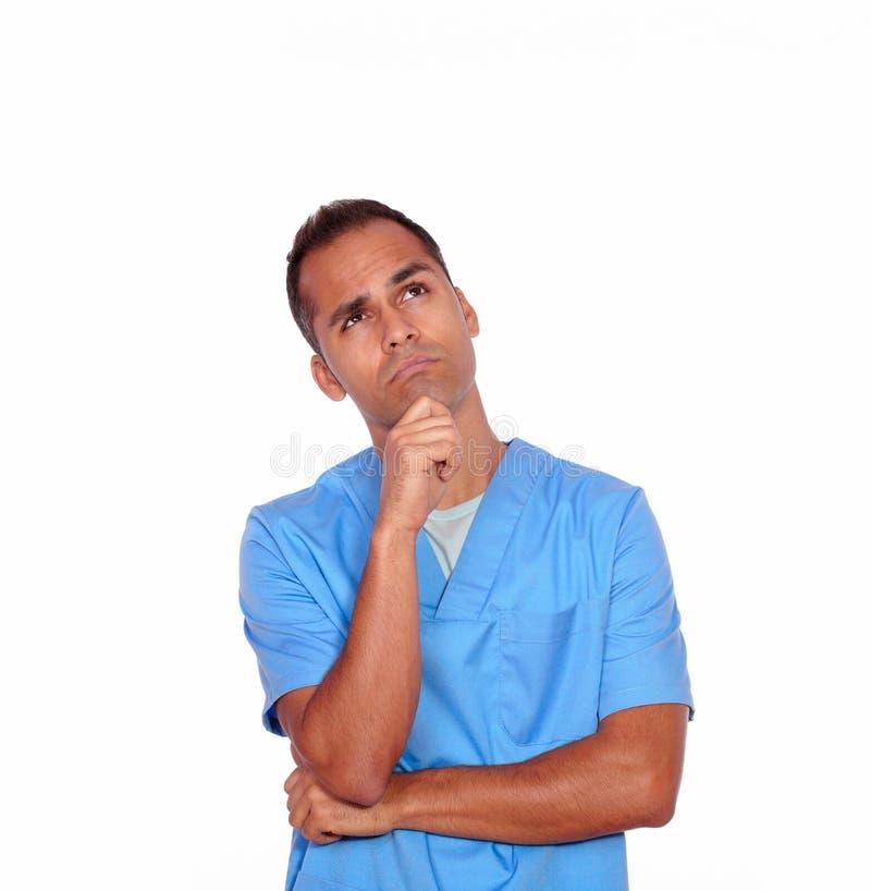 Enfermera pensativa del muchacho que se coloca con la mano en la barbilla fotos de archivo