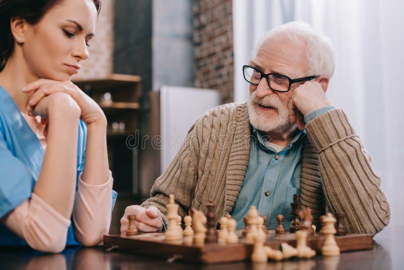 Enfermera pensativa y un más viejo hombre imagenes de archivo