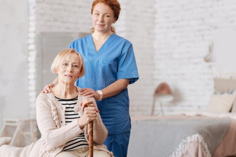 Enfermera privada calificada que ayuda al paciente mayor imagen de archivo libre de regalías
