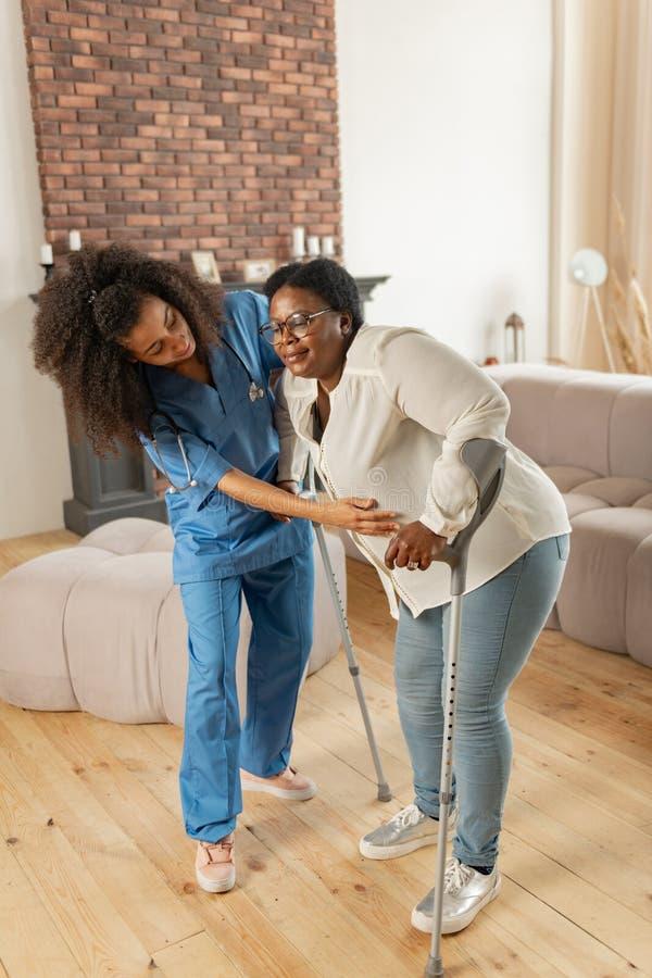 Enfermera privada que ayuda a la mujer envejecida después de cirugía de la pierna en su hogar fotografía de archivo libre de regalías