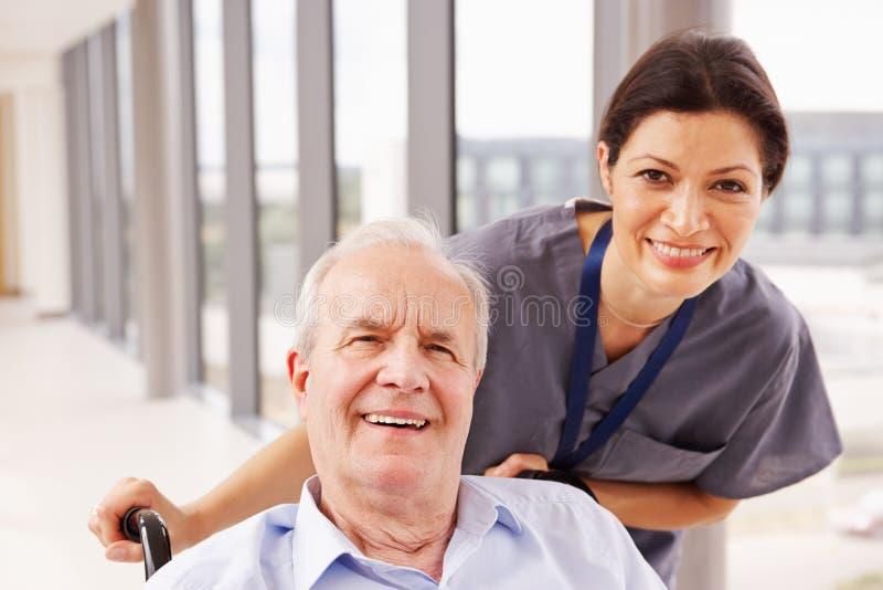 Enfermera Pushing Senior Patient en silla de ruedas a lo largo del pasillo imagen de archivo