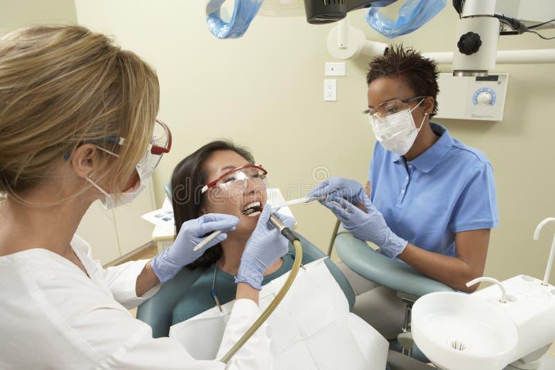 Enfermera que ayuda al doctor While Treatment fotografía de archivo libre de regalías