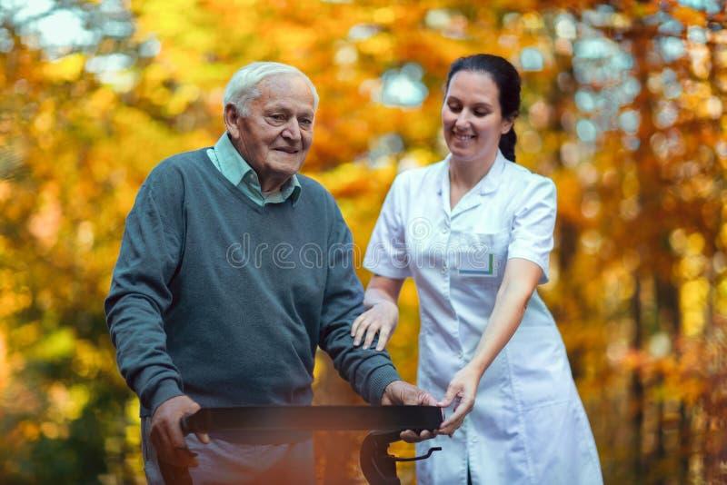 Enfermera que ayuda al hombre mayor mayor fotografía de archivo libre de regalías