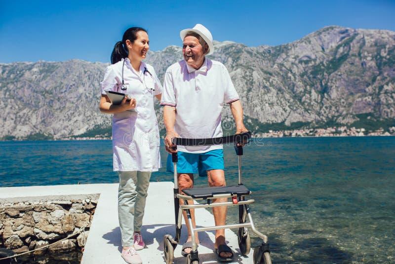 Enfermera que ayuda al hombre mayor mayor imagen de archivo libre de regalías