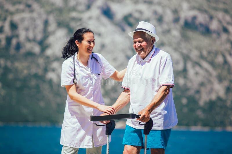 Enfermera que ayuda al hombre mayor mayor imagenes de archivo