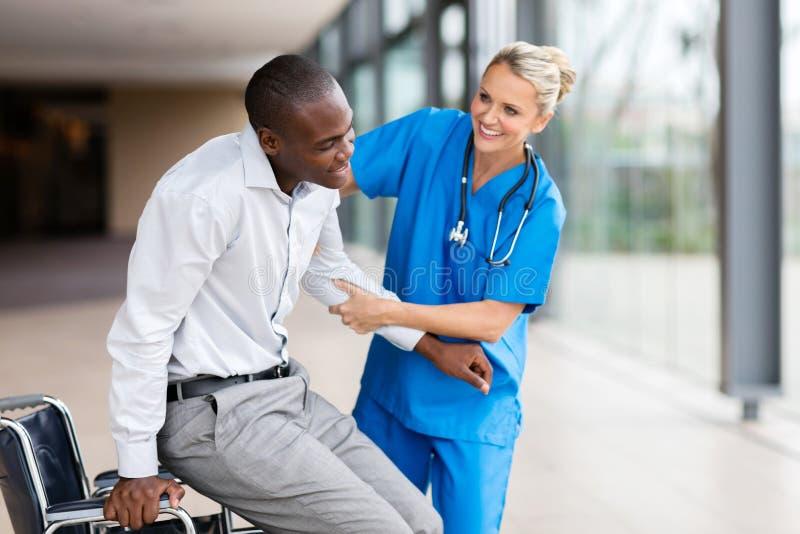 enfermera que ayuda al hombre perjudicado imágenes de archivo libres de regalías