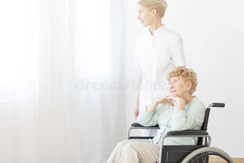 Enfermera que ayuda a la mujer mayor imagenes de archivo
