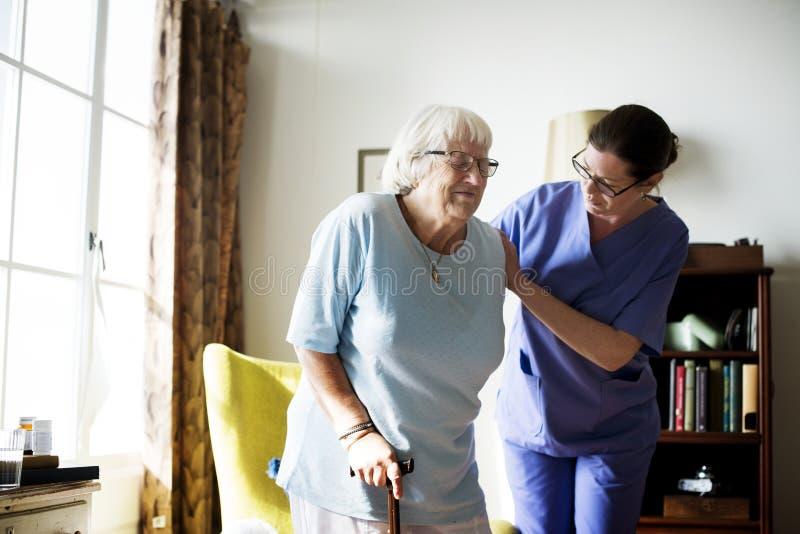 Enfermera que ayuda a la mujer mayor a colocarse imagenes de archivo