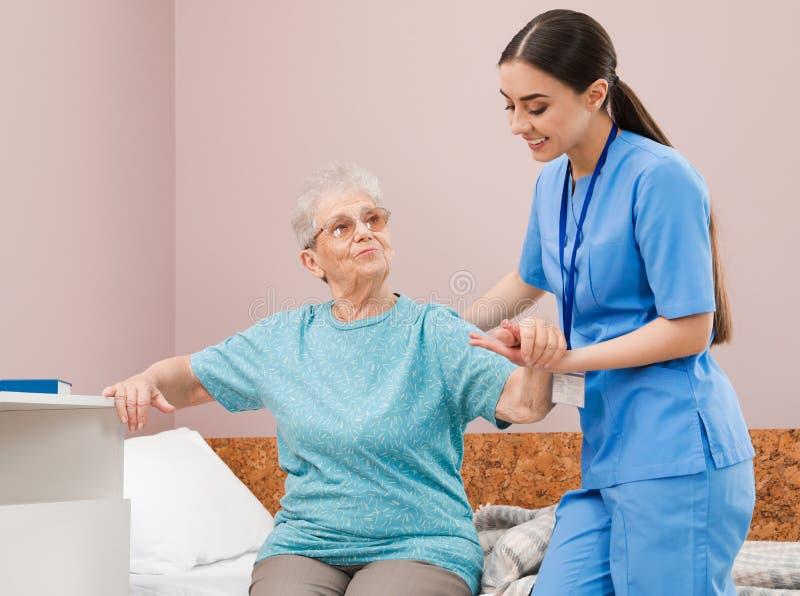 Enfermera que ayuda a la mujer mayor en cama fotos de archivo libres de regalías