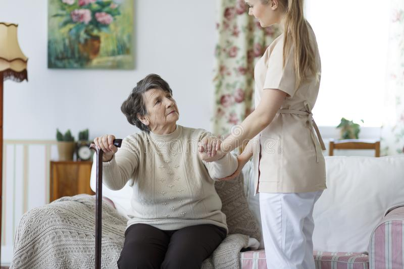 Enfermera que ayuda a la mujer mayor a levantarse fotografía de archivo libre de regalías