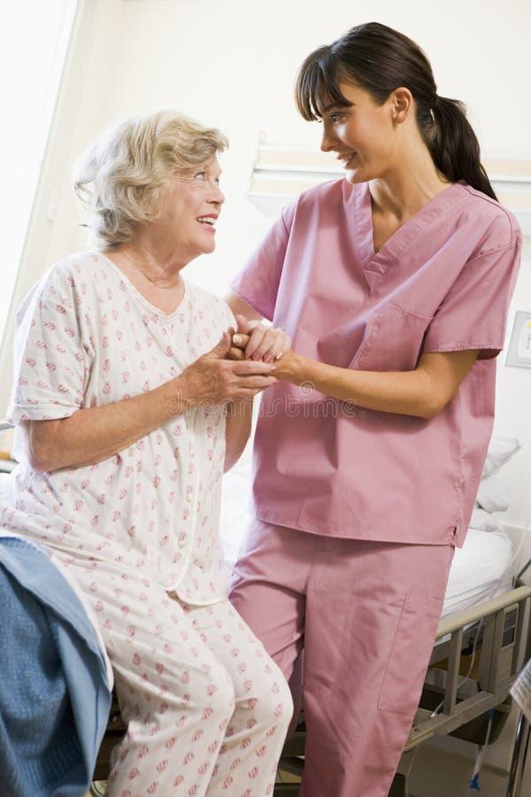 Enfermera que ayuda a la mujer mayor a recorrer fotos de archivo